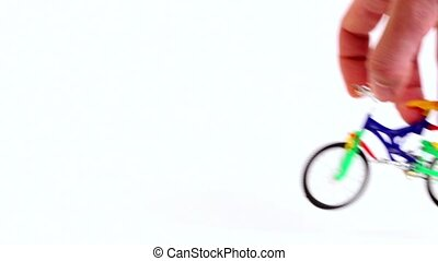Hand does jump trick on toy bicycle and leave, then repeats...