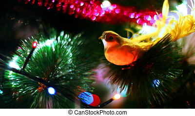 yellow bird toy sits on Christmas tree among of blinking...