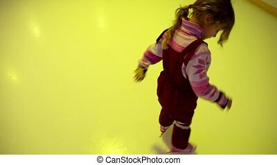 Little girl skates on ice rink, colored light flashes