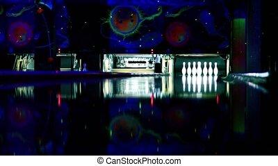 Skittles at bowling lane lit in dark club, people throw...