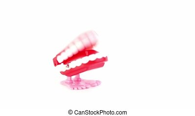 Little toy jaw jumps and clicks teeth, isolated on white...