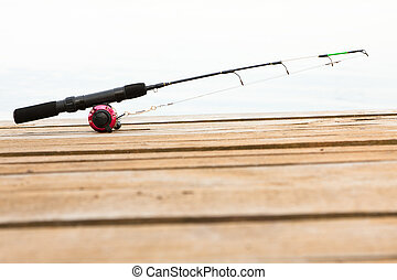 Fishing rod and reel on a deck - Unattended fishing rod,...