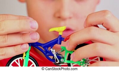 Boy hold toy bike in front of his face, he push and moves...