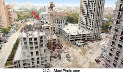 Construction site in foreground of cityscape of dormitory...