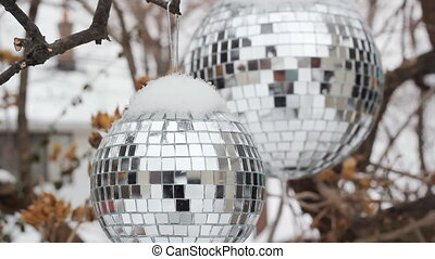 Winter disco balls - Two disco balls hanging outside on a...