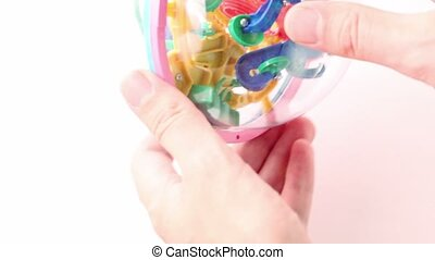 Hands rotate three-dimensional toy puzzle within which ball...