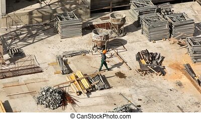 worker goes on building site among building materials