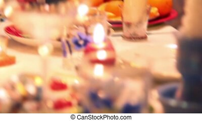 Candles and glasses on decorated christmas dining table,...