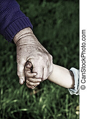grandmother holds childs hand outdoor