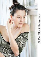 Portrait of pretty brunette girl in window