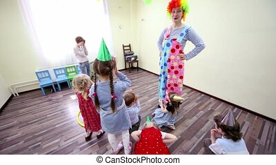 Two clowns play with kids at birthday celebration in club...