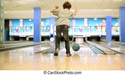 Little boy throws bowling ball to beat skittles, view from behind