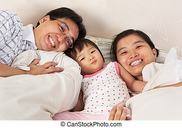 Chinese family having fun on bed
