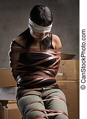 Woman being kidnapped - A young woman tied-up, blind folded...