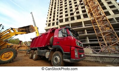 Excavator loads truck at construction site of living house