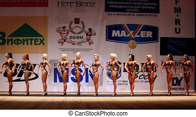 Twelve bodybuilders female poses at Open Cup of bodybuilding and fitness of Moscow