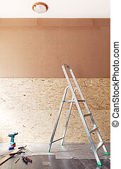 Work tools and ladder in front of new blank unfinished wall made of plywood