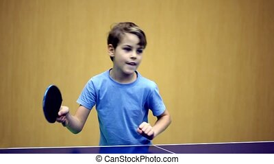 Little boy wearing blue shirt playing ping pong, he got...