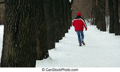 Man snake runs among trees on park alley at winter day
