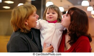 Grandmother and mother kiss little girl inside cafeteria -...