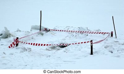 Enclosure square area with ice hole for winter swimming in middle of snow pile