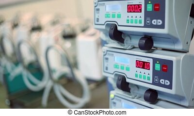 Some medical equipment stand in row, infusion pump for...