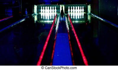 Two bowling lanes lit in dark club, bolls roll and beat tenpins