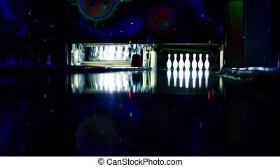 Machine set up tenpins at bowling lit in dark club, balls...