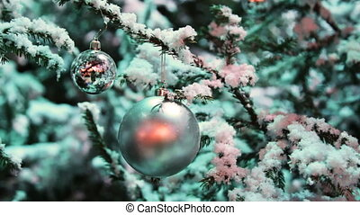 two glass balls silver color hang on snow covered fir in winter forest