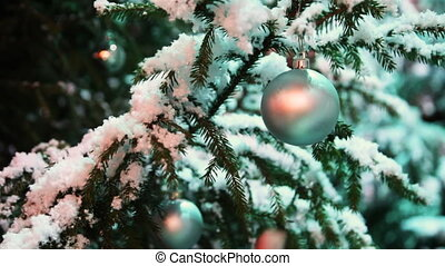 glass ball hangs on snow covered fir in forest, gentle female hand touches it