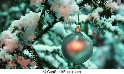 glass ball silver color hangs on snow covered fir in winter forest