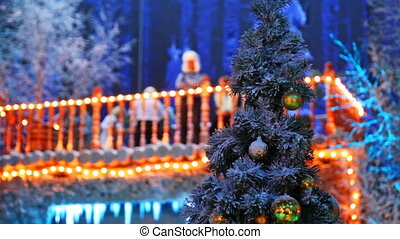christmas tree and behind it in defocus woman on terrace...