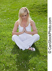 Serenity through yoga - A pretty blonde girl sits on the...