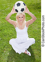 Smiling blonde holding a soccerball