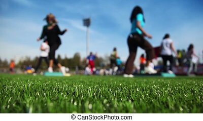 Women engaged in step aerobic on stadium in sunny autumn...