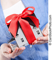 Hands holding house model with red bow