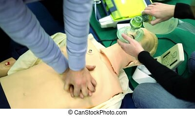 Person trains to do chest compressions and artificial...