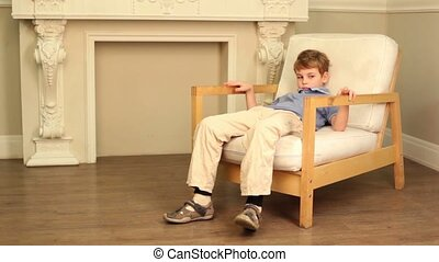 Boy sits in chair beside the fireplace - Boy sits in soft...