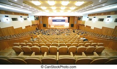 Many people sit in large hall with wooden chairs at...