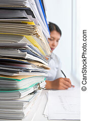 Paperwork and worker - Lots of workload with people working...