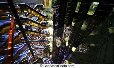 Several escalators and elevators on multiple floors trade...