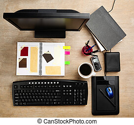 Designer working desk filled with computer, scarpbook and...