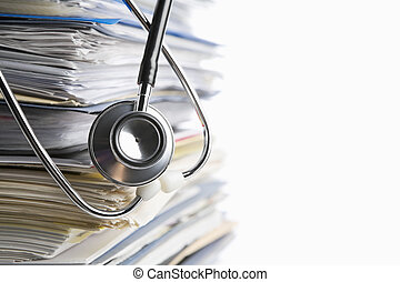 Medical record concept with stetoschope over pile of...