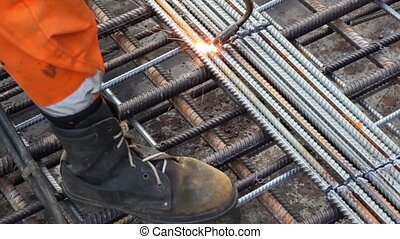 Worker legs weld metal grating by acetylene torch - Worker...