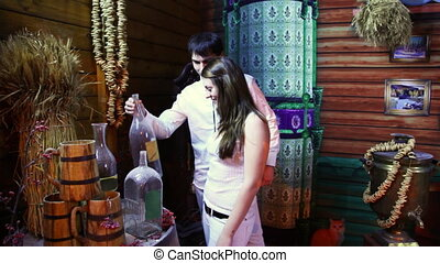 couple stands in ancient wooden house and sees old bottles -...