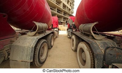 Two concrete mixer stand near unfinished tall high-rise buildings