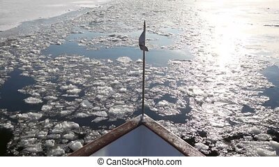 Flag fly in bow of ship, which floats on river with cracked ice