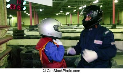 Carting trainer helps little boy to put on helmet, at ground...