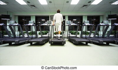 man goes on treadmill in large empty gym, wide view