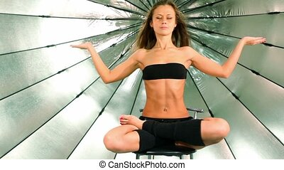 girl sits with folded legs and hands raised, she meditates -...